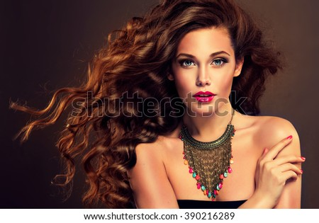 Shutterstock Beautiful model brunette with long curled hair and jewelry necklace .  Hairstyle small Curling