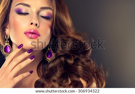 Beautiful model brunette with long curled hair. Purple manicured nails and jewelry earrings