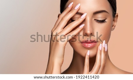 Beautiful model girl with a French manicure nails. Woman Fashion makeup and care for hands cosmetics. Facial treatment . Cosmetology,beauty and spa. Skin care