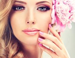 Beautiful model girl , with a smile and flowers  peony near the face .  Soft pink makeup and manicure on nails . Cosmetics , beauty and cosmetology .