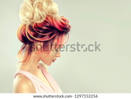 Beautiful model girl  with elegant  multi colored hairstyle . Stylish Woman with fashion  hair  color highlighting.   Creative  red and pink roots ,   trendy  coloring.  #1297152256