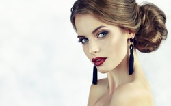 Beautiful model girl with fashionable make-up and hairstyle . Beauty, accessories and jewelry earrings.