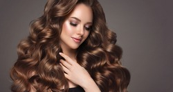 Beautiful model girl with long wavy and shiny hair . Brunette woman with curly hairstyle