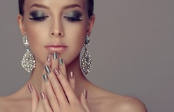 Beautiful model girl with pink and silver  metallic manicure on nails . Fashion makeup smokey eyes and cosmetics . Big silver diamond Shine  earrings jewelry .