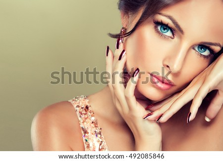 Beautiful model girl with pink metallic manicure on nails . Fashion makeup and cosmetics . Pink dress with rhinestones