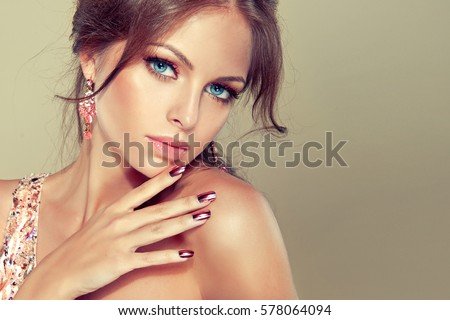 Beautiful model girl with pink metallic manicure on nails . Fashion makeup and cosmetics . Pink dress with rhinestones and pink earrings jewelry .