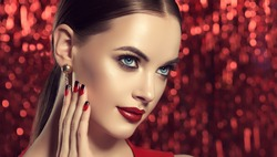 Beautiful model girl with red and black  french manicure on nails . Fashion luxury makeup . Cherry color lips and shiny eye shadow pigment . Beauty  and cosmetics . Brilliant flickering  background