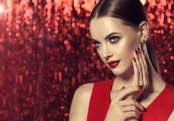 Beautiful model girl with red and black  french manicure on nails . Fashion luxury makeup . Dark red lips and shiny eye shadow pigment . Beauty  and cosmetics . Red brilliant background .
