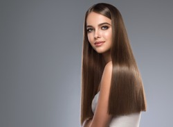 Beautiful model girl with shiny brown and straight long hair. Keratin  straightening. Treatment, care and spa procedures. Smooth hairstyle