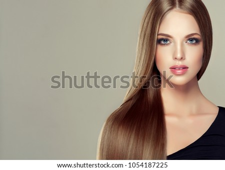Beautiful model girl with shiny brown and straight long  hair . Keratin  straightening . Treatment, care and spa procedures. Smooth hairstyle #1054187225