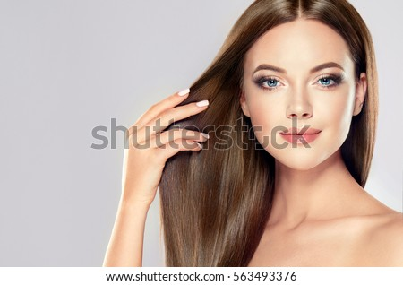 Beautiful model girl with shiny brown straight long  hair . Care and hair products . #563493376