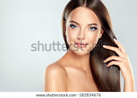 Beautiful model girl with shiny brown straight long  hair . Care and hair products .