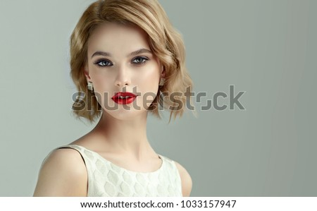 Beautiful model girl with short curly  hair and red lips .