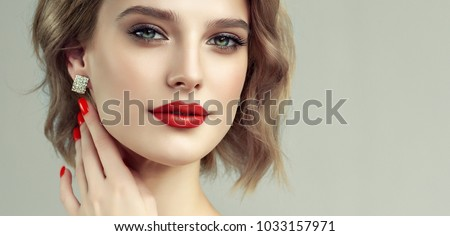 Beautiful model girl with short curly  hair and red lips . Red manicure on nails .Beauty and esthetic care . Modern styling for blonde haired. Earrings jewelry and accessories