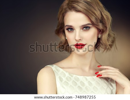 Beautiful model girl with short curly  hair and red lips . Red manicure on nails .Beauty and esthetic care  #748987255
