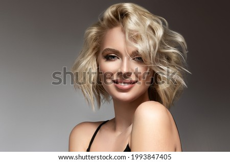 Beautiful model girl with short hair .Beauty woman with blonde curly hairstyle dye .Fashion, cosmetics and makeup