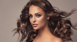 Beautiful model girl with wavy and shiny hair . Brunette woman with curly hairstyle
