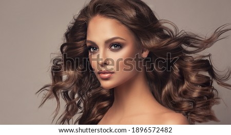 Beautiful model girl with wavy and shiny hair . Brunette woman with curly hairstyle Foto stock ©