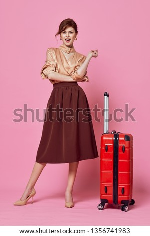 beautiful model in a long skirt and in a silk shirt stands near a red suitcase