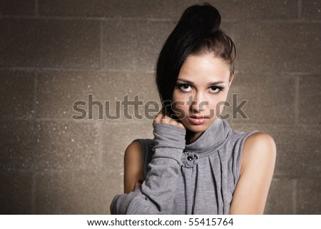 Beautiful model in gray dress on brick wall background - stock photo