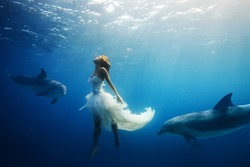 Beautiful model in white dress underwater. A girl diving with dolphins without scuba gear. Fantasy mermaid in deep ocean. Water surface with sunbeams.