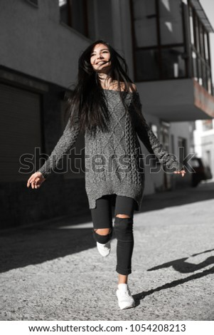 Beautiful model poses for the camera on the streets. #1054208213