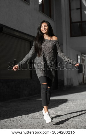 Beautiful model poses for the camera on the streets. #1054208216