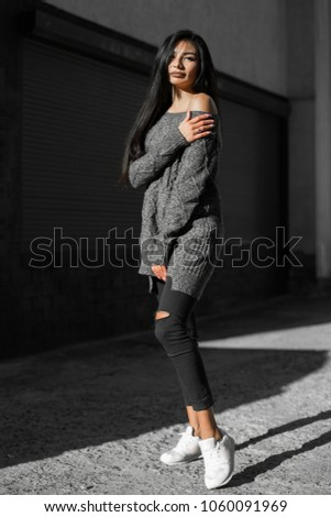 Beautiful model poses for the camera on the streets. #1060091969