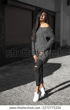 Beautiful model poses for the camera on the streets. #1273775326