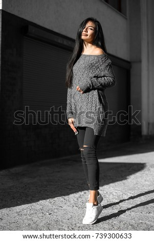 Beautiful model poses for the camera on the streets. #739300633