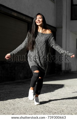 Beautiful model poses for the camera on the streets. #739300663