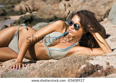 Beautiful model relaxing on a beach in Costa Brava, Spain.