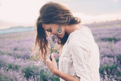 Beautiful model walking in spring or summer lavender field in sunrise backlit. Boho style clothing and jewelry.