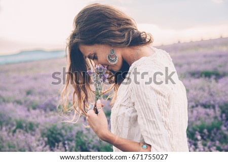Beautiful model walking in spring or summer lavender field in sunrise backlit. Boho style clothing and jewelry. #671755027
