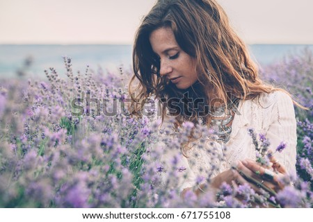 Beautiful model walking in spring or summer lavender field in sunrise backlit. Boho style clothing and jewelry. #671755108
