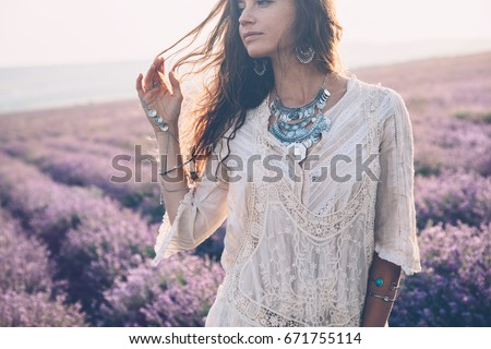 Beautiful model walking in spring or summer lavender field in sunrise backlit. Boho style clothing and jewelry. #671755114