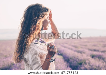 Beautiful model walking in spring or summer lavender field in sunrise backlit. Boho style clothing and jewelry. #671755123