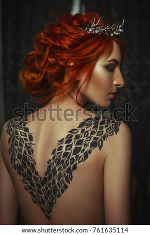 Stock Photo Beautiful model wearing creative body art dress is posing in a dark studio