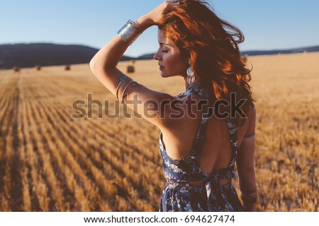 Beautiful model wearing summer cotton maxi dress and bracelets posing in autumn field with hay stack. Boho style clothing and jewelry. #694627474