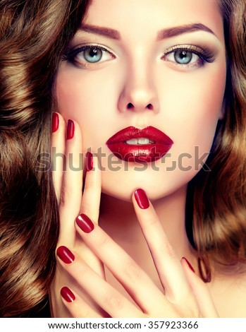 Beautiful model with curly hair and red manicure closeup . fashion trend image ,the girl with blue eyes , fashion makeup and red nails