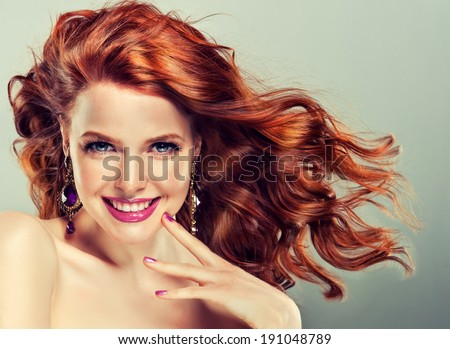 Beautiful model with curly red hair and fashion earrings