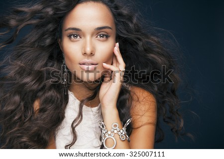 beautiful model with wavy hairstyle and accessories. Portrait of young woman with makeup and fresh skin. Blowing hair. Toned in warm colors. Studio shot, horizontal