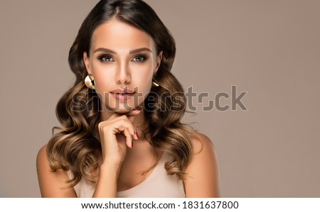 Beautiful model woman have wavy and shiny hair . Brunette girl with curly hairstyle,earrings and jewelry