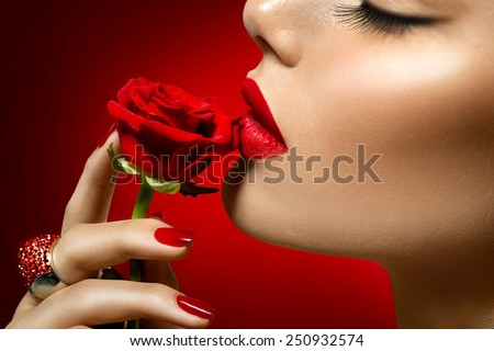 Beautiful Model woman kissing red rose flower. Red Lips, Nails and Rose. Beauty Girl. Makeup and Manicure. Sensual Mouth. Sexy Red Color Lips. St. Valentine\'s Day design. Part of Face