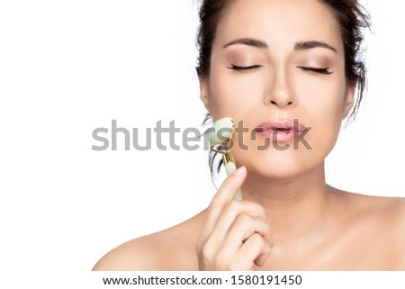 Beautiful model woman with healthy fresh clean skin enjoying a massage with a jade face roller to improve circulation, relax the muscles and tone the skin, isolated on white background with copy space