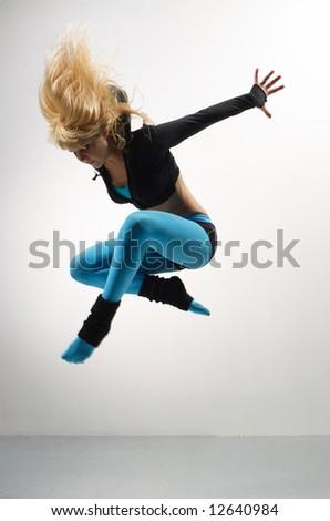 beautiful modern ballet dancer posing on grey background - stock photo