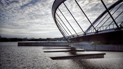 Beautiful modern bridge with a scenery landscape and a cumulus clouds in Putrajaya Malaysia. Image has grain or blurry or noise and soft focus when view at full resolution.