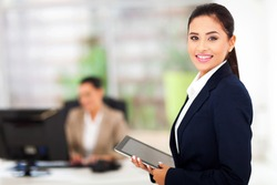 beautiful modern businesswoman holding tablet computer with colleague on background