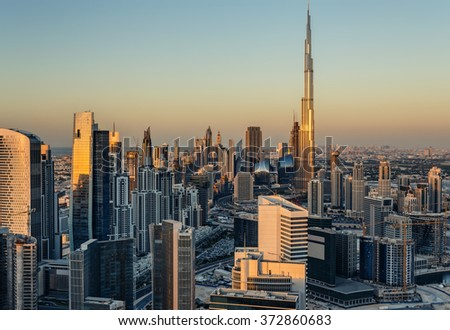 Beautiful modern city architecture at golden sunset. View of Dubai\'s business bay towers.