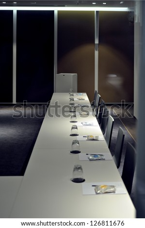 Beautiful modern empty conference room with large conference table. Small snacks, drinks and documents, pencils already prepared and are already in front of each participant
